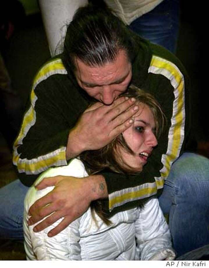 A woman is comforted at the scene of an explosion outside a nightclub near Tel Aviv's beach front promenade late Friday Feb. 25, 2005. A suicide bomber blew himself up among Israelis waiting outside the nightclub just before midnight Friday, killing at least three people, wounding dozens and shattering an unofficial Mideast truce.(AP Photo/Nir Kafri) ** ISRAEL OUT MAGAZINES OUT **