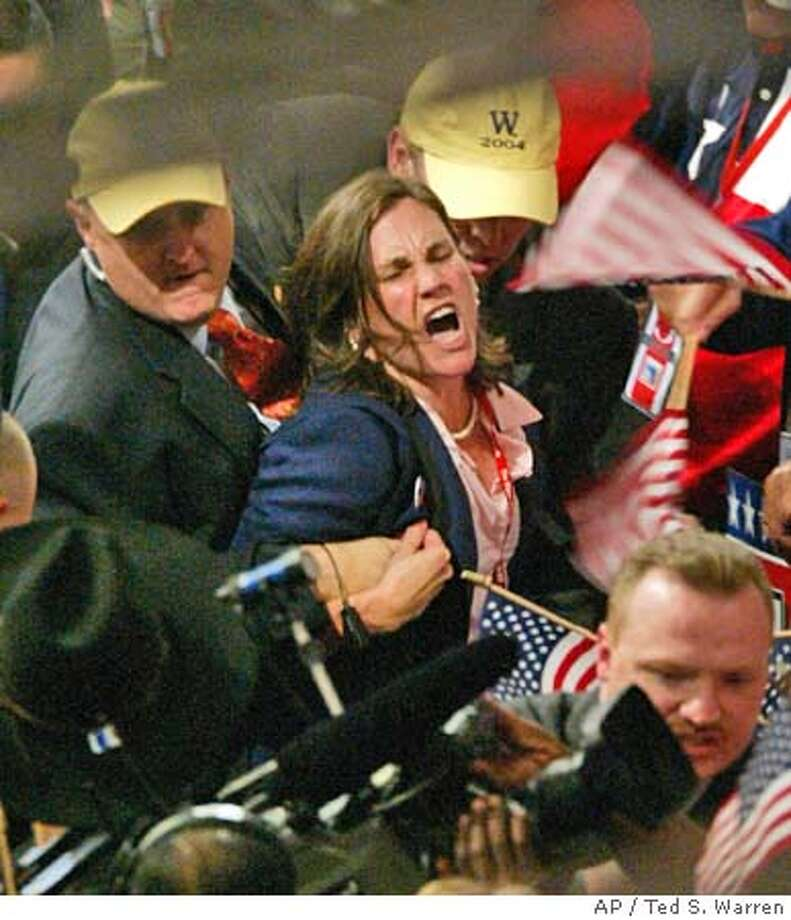An unidentified protester is escorted off the convention floor on the final night of the Republican National Convention Thursday, Sept. 2, 2004, in New York. (AP Photo/Ted S. Warren) Photo: TED S. WARREN