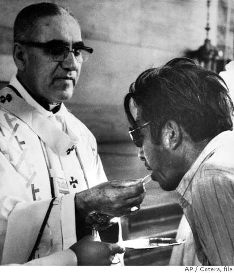 ** FILE ** Archbishop Oscar Arnulfo-Romero offers the host wafer during the communion rite to a member of the congregation during a church mass in San Salvador, El Salvador on Jan. 13, 1980. A retired officer from El Salvador is being sued Tuesday August 24, 2004 in Fresno federal court on allegations that he conspired in the 1980 assassination of Latin American human rights figure El Salvador's Archbishop Oscar Romero as he held mass in a crowded cathedral in the capital, San Salvador. (AP Photo/Cotera, file) JAN. 13, 1980 FILE PHOTO Photo: COTERA