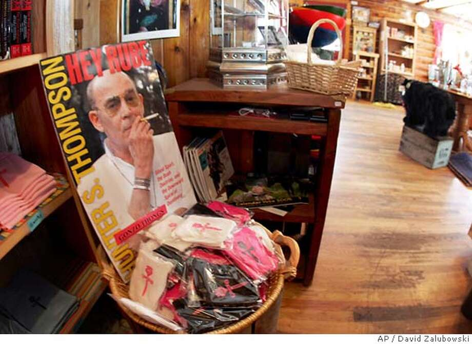 A poster of gonzo journalist Hunter S. Thompson sits on a bin of thong underwear bearing his logo for sale in the Woody Creek Store in Woody Creek, Colo., Monday, Feb. 21, 2005. Thompson, who lived in the tiny hamlet north of Aspen, Colo., was found dead in his home at the age of 67 on Sunday from an apparent self-infliced gunshot wound. (AP Photo/David Zalubowski) Photo: DAVID ZALUBOWSKI