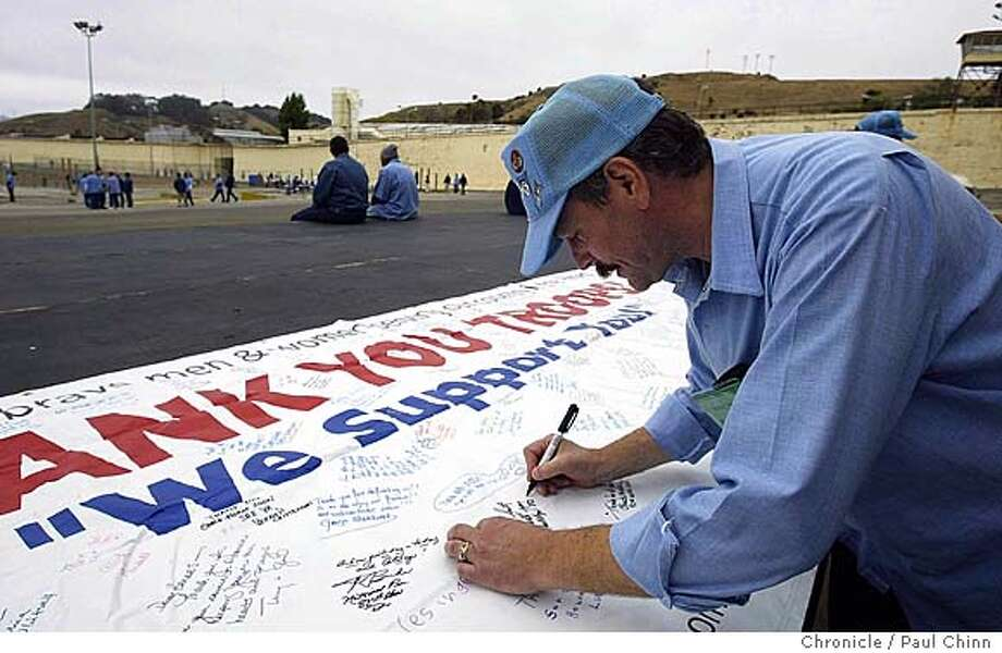 Inmate Mike Northrop signed a large banner unrolled in the exercise yard that will be sent to the troops along with the 800 care packages. Inmates from the Vietnam Veterans Group of San Quentin packed boxes of goodies for troops serving in Iraq in San Quentin on 7/31/04. PAUL CHINN/The Chronicle Photo: PAUL CHINN