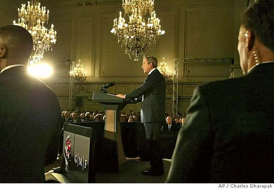 U.S. President Bush, center, is guarded by U.S. Secret Service agents as he speaks to European business people, diplomats, and academics at Concert Noble in Brussels, Belgium, Monday, Feb. 21, 2005. (AP Photo/Charles Dharapak) Photo: CHARLES DHARAPAK