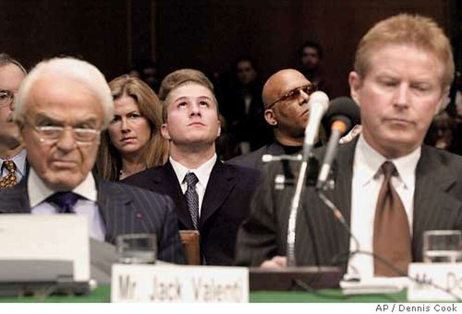 Napster founder Shawn Fanning, center, listens as the Senate Judiciary Committee holds a hearing on online entertainment Tuesday, April 3, 2001, on Capitol Hill in Washington. Jack Valenti, president of the Motion Picture Association of America, is at left and recording artist Don Henley is at right. (AP Photo/Dennis Cook) Ran on: 08-30-2004 Photo: DENNIS COOK