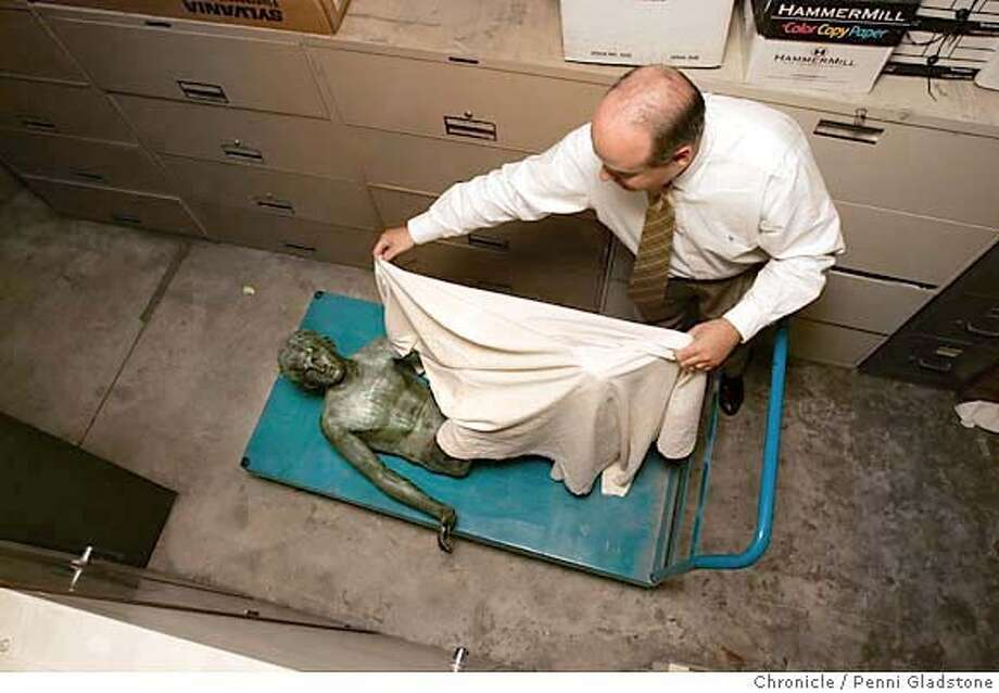 Deke Kastner, gen mgr. of the Club covers statue up which sits in the basement. Hermes, a statue that was stolen from SF's University Club two weeks ago is now back home. 8/31/04 in San Francisco.  Penni Gladstone / The Chronicle Photo: Penni Gladstone