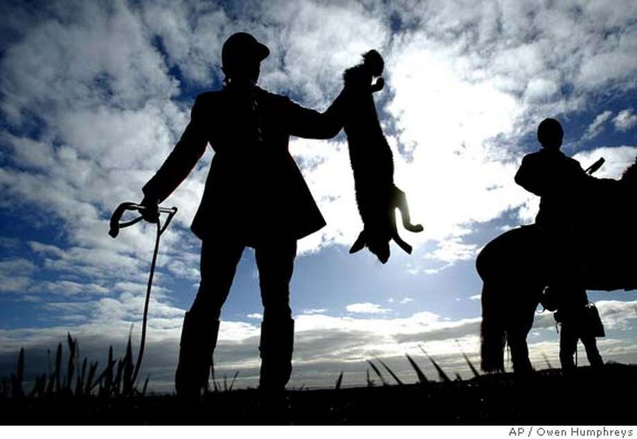 A huntsman holds up a fox after it was shot in the South Durham Hunt, near Sedgefield Saturday Feb. 19, 2005. A controversial new law banning the hunting and killing of foxes with hounds in England and Wales came into effect Friday but thousands of people were expected to attend hundreds of hunt meetings throughout England and Wales, most of which were expected to reluctantly follow the new rules. (AP Photo/Owen Humphreys,PA) ** UNITED KINGDOM OUT PHOTOGRAPH CANNOT BE STORED OR USED FOR MORE THAN 14 DAYS AFTER THE DAY OF TRANSMISSION ** Photo: OWEN HUMPHREYS