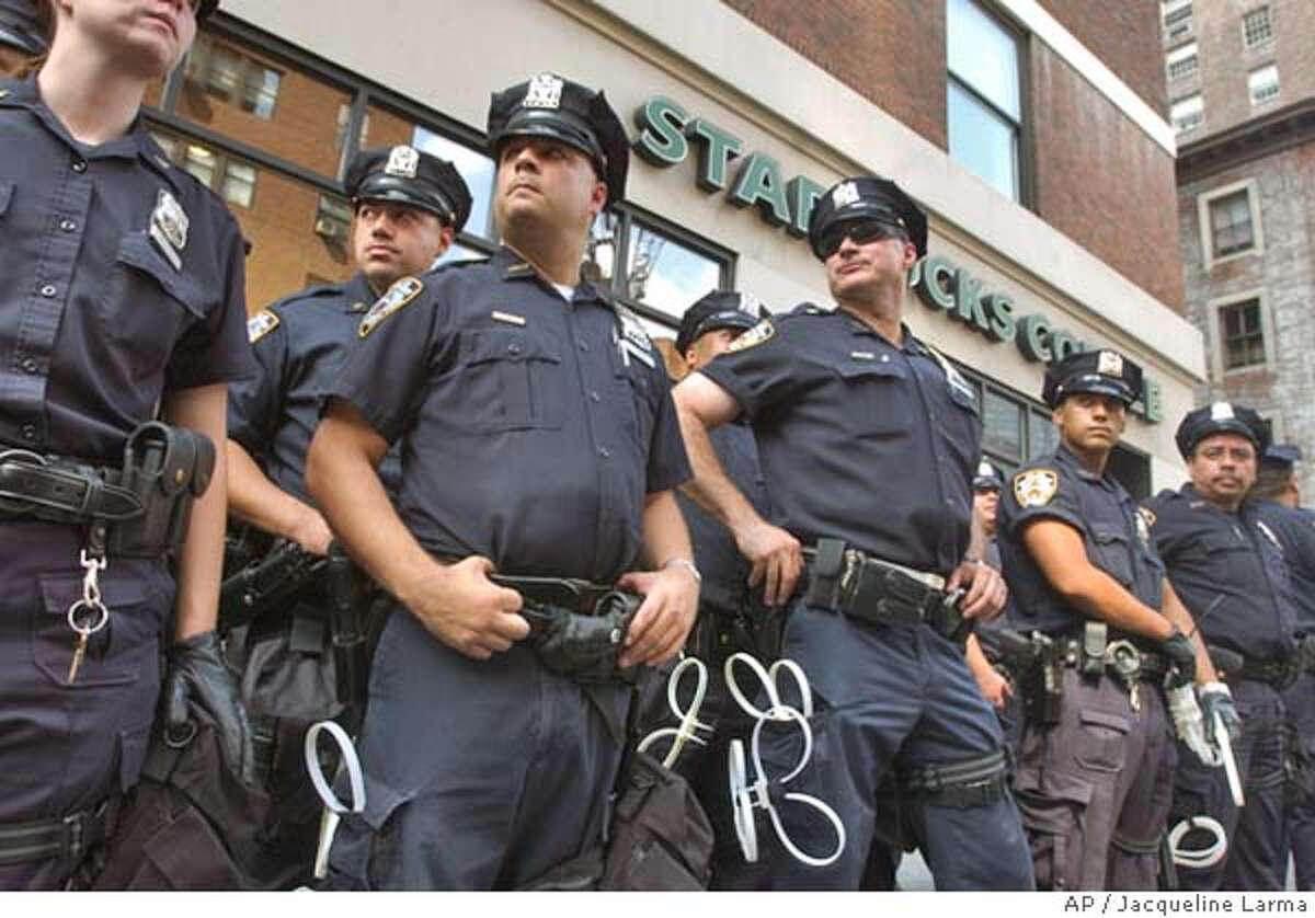 New York police form a barrier in front of a during a Starbucks coffee shop during a demonstration against Starbucks' workplace practices and the Bush administration's alleged support for the chain's anti-union practices in New York Saturday Aug. 28, 2004. The Republican National Convention is scheduled to begin in New York on Monday. (AP Photo/Jacqueline Larma)