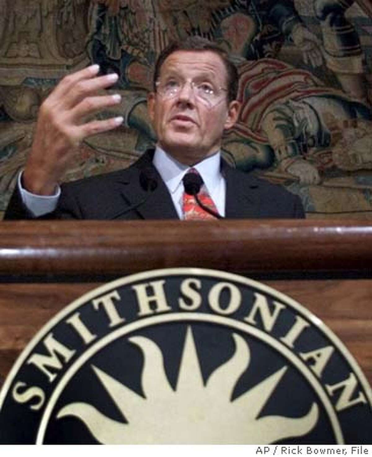 **FILE** Smithsonian Institution Secretary Lawrence Small speaks during a Washington news conference in this May 7, 2001 file photo. Small, the head of the Smithsonian Institution, will plead guilty to violating a federal law protecting endangered birds, the agency announced Tuesday, Jan. 20, 2004. (AP Photo/Rick Bowmer, File) Lawrence Small bought the headdresses before he was hired to run the Smithsonian. A MAY 7, 2001 FILE PHOTO