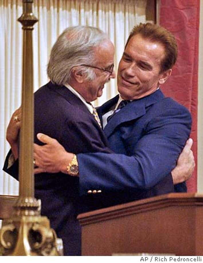 State Sen. President Pro Tem John Burton, D-San Francisco, left, gets a hug from Gov. Arnold Schwarzenegger, during the last day of the Legislative session held at the Capitol in Sacramento, Calif., Friday, Aug. 27, 2004. Schwarzenegger made surprise visit to the Senate to honor Burton, who has served 25 years in the legislature and is leaving office due to term limits. (AP Photo/Rich Pedroncelli) Photo: RICH PEDRONCELLI