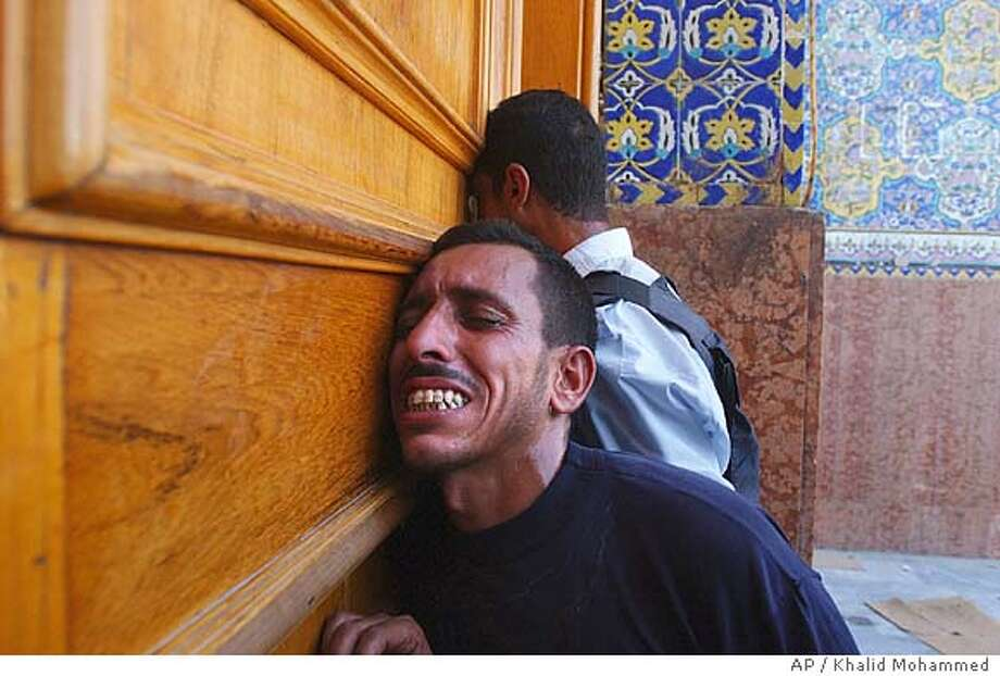 Iraqi police pray at the door of the Imam Ali shrine, one of Shiite Islam's holiest, which has served as a base for al-Sadr's fighters and been at the center of much of the three-week crisis in the southern Iraqi city of Najaf Friday Aug. 27, 2004. Guns were largely silent in Najaf on Friday for the first time in weeks, after Iraq's top Shiite cleric made a dramatic return to this holy city and swiftly won agreement from a rebel cleric and the government to end three weeks of fighting between his militia and U.S.-Iraqi forces. (AP Photo/Khalid Mohammed) Photo: KHALID MOHAMMED