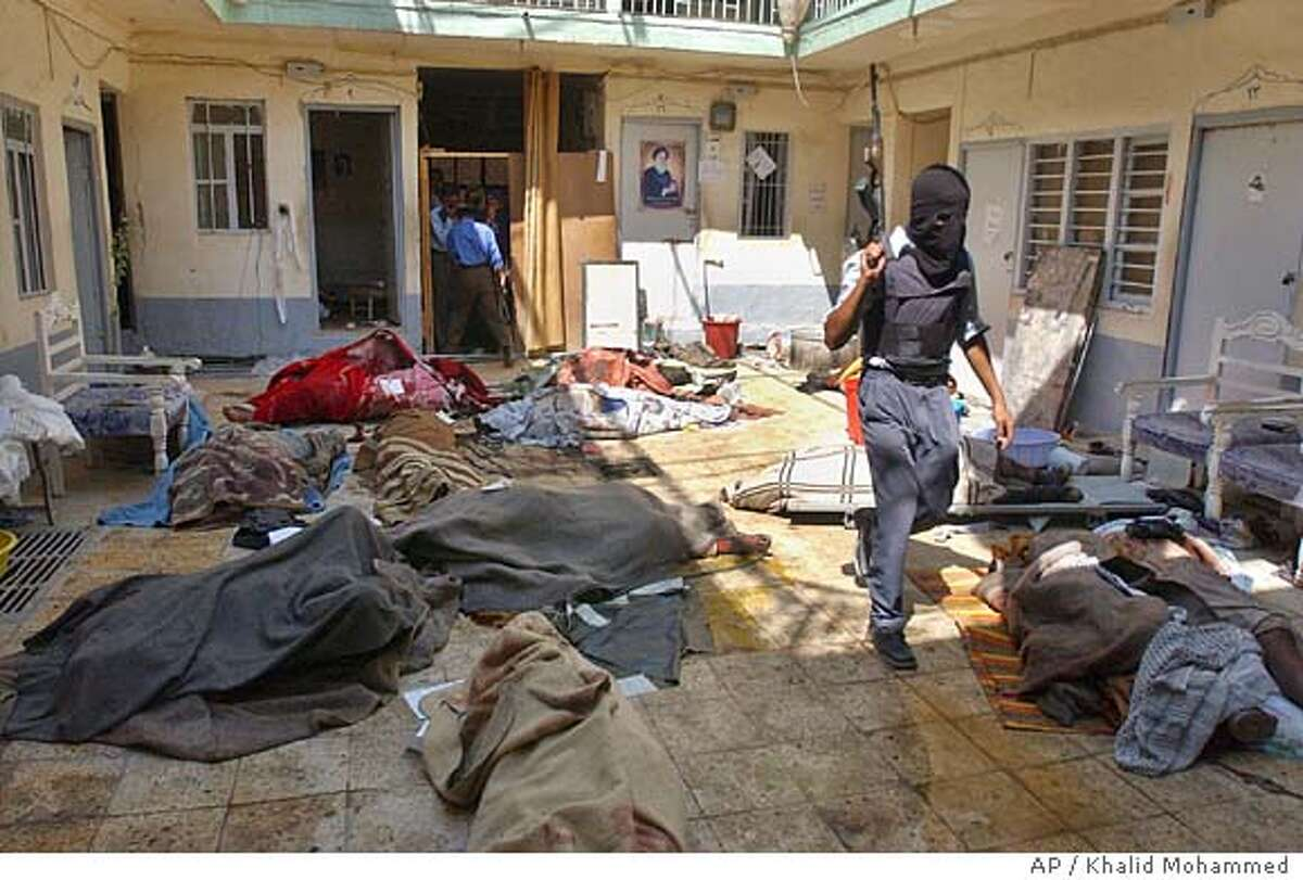 An Iraqi police officer inspects the area where about 10 bodies were discovered in a maverick religious court run by rebel Shiite cleric Muqtada al-Sadr's followers in the southern city of Najaf, Iraq Friday Friday Aug. 27, 2004. Al-Sadr's office in Najaf set up the court, which ordered arrests and meted out punishments outside of religious and legal authorities. Local Iraqi officials have in the past demanded the court be shut down and all prisoners freed. (AP Photo/Khalid Mohammed)