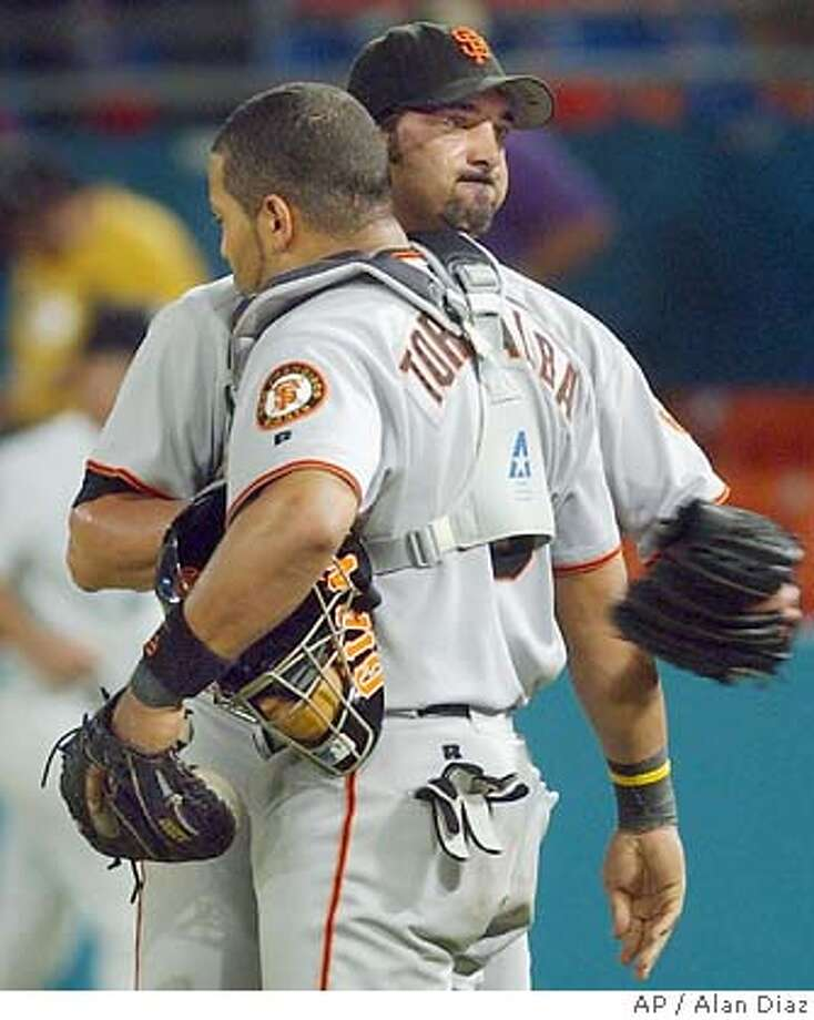 San Francisco Giants relief pitcher Dustin Hermanson, background, celebrates with catcher Yorvit Torrealba, foreground, the 6-5 win over the Florida Marlins in ten innings Wednesday, Aug. 25, 2004 in Miami. (AP Photo/Alan Diaz) Photo: ALAN DIAZ
