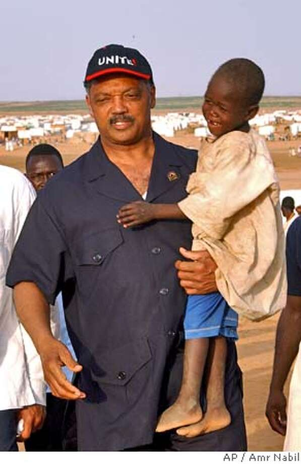 American civil rights activist, Rev. Jesse Jackson, carries a Sudanese displaced child during his visit to Abu Shouk camp, in North Darfur, Sudan, where more than 40,000 displaced people receive food and shelter from international aid agencies, Friday, Aug.27, 2004. (AP Photo/Amr Nabil) Photo: AMR NABIL