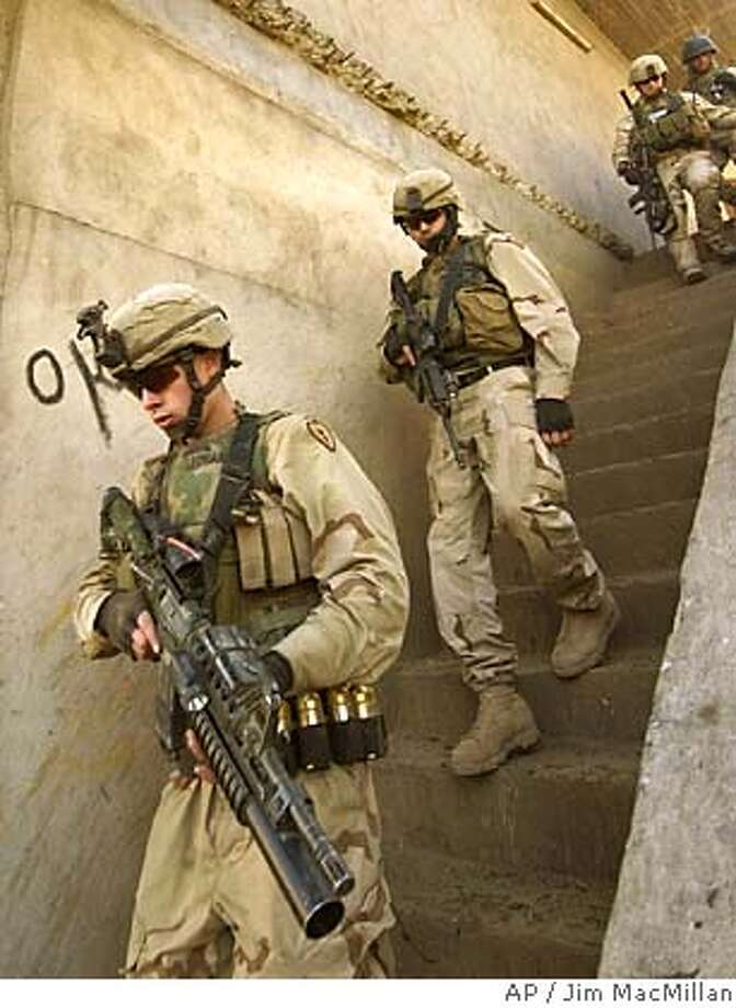U.S. Army 1st Battalion, 24th Infantry Regiment soldiers search for insurgents in Mosul, Iraq Monday Feb. 14, 2005. At least nine insurgents were killed in a running gun battle with U.S. forces in Mosul Saturday. (AP Photo/Jim MacMillan) Photo: JIM MACMILLAN