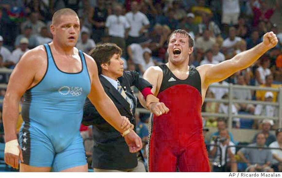 Gerogiy Tsurtsumia, from Kasakhstan, right, celebrates after defeating Rulon Gardner, from the United States, during a men's greco-roman 120kg wrestling semifinal bout at the 2004 Olympic Games in Athens, Wednesday, Aug. 25, 2004. (AP Photo/Ricardo Mazalan) Photo: RICARDO MAZALAN