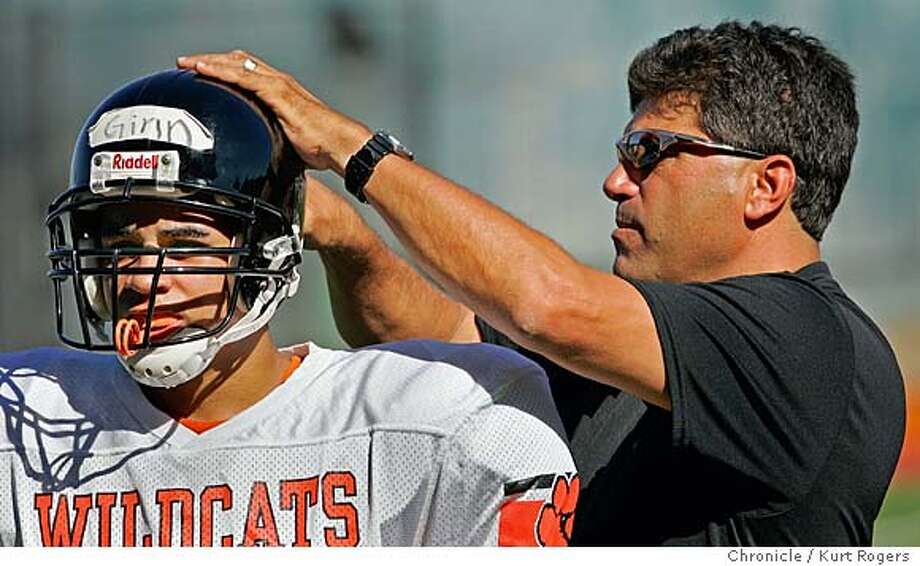 On the first day with full pads coach Steve Nicolopulos helps Prentig Ginn with his helmet.  Woodside football had a miserable 2003 season and is trying to recover 7/18/04 in Woodside,CA.  Kurt Rogers/The Chronicle Photo: Kurt Rogers