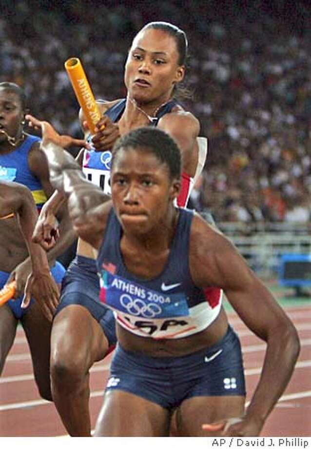 United States' Marion Jones passes the baton to Lauryn Williams in round 1 of the 4 x 100-meter relay at the Olympic Stadium during the 2004 Olympic Games in Athens, Thursday Aug. 26, 2004. The United States won the heat. (AP Photo/David J. Phillip) Photo: DAVID J. PHILLIP