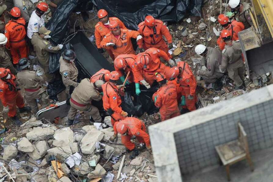 Rescue workers pull the body of a victim from the rubble after a building collapsed in Rio de Janeir