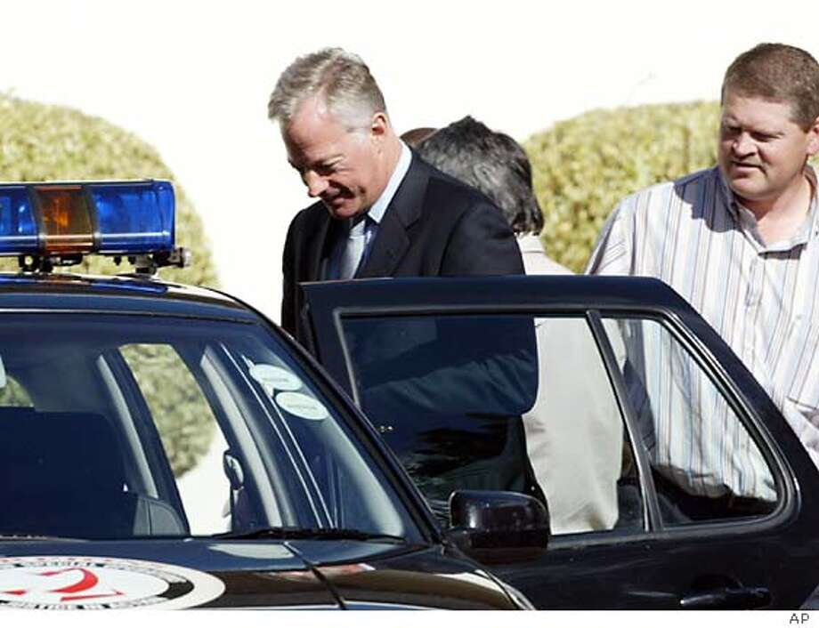 Mark Thatcher, left, wearing suit, the son of former British Prime Minister, Margaret Thatcher is escorted by police outside his home in Cape Town, South Africa, Wednesday Aug. 25, 2004. Thatcher was arrested on allegations he was involved in a plot to overthrow the government of oil-rich Equatorial Guinea. (AP Photo) **SOUTH AFRICA OUT**
