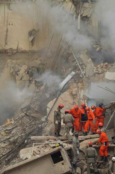 Rescue workers carry the body of a victim after a building collapsed in Rio de Janeiro, Brazil, Thur