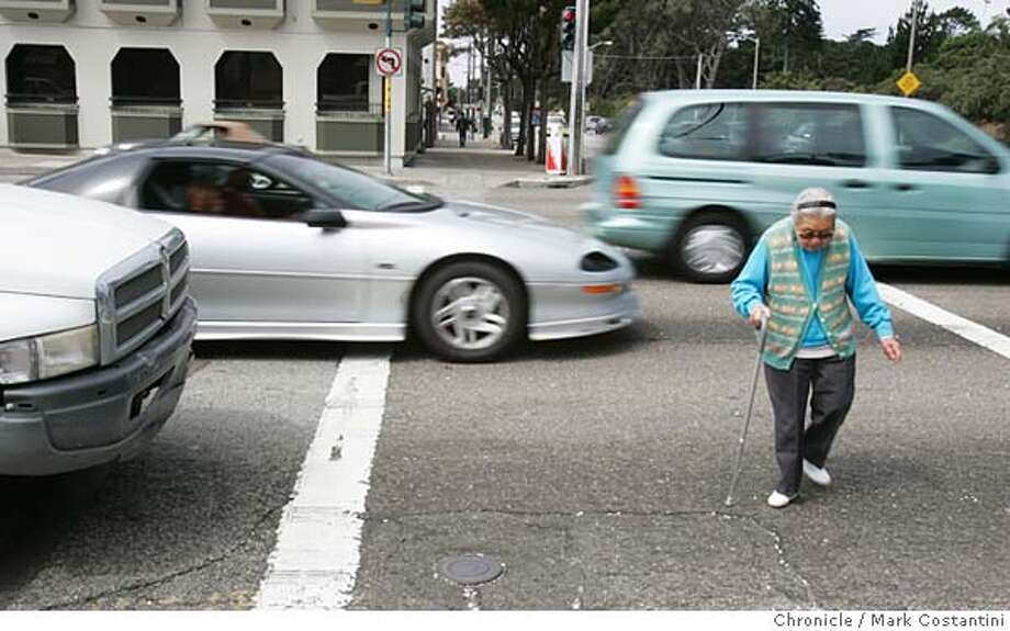 AN ELDERLEY WOMAN WITH CANE CROSSES INTERSECTION AS CARS SPEED THROUGH INTERSECTION.  INTERSECTION OF NORTHBOUND 19TH AVE. AT LINCOLN, WHERE A PEDESTRIAN WAS KILLED BY A CAR LAST NIGHT. Event on 8/25/04 in SAN FRANCISCO. S.F. Chronicle Photo: Mark Costantini Photo: Mark Costantini