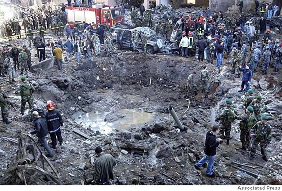 Rescue workers and soldiers stand around a massive crater after a bomb attack that tore through the motorcade of former Prime Minister Rafik Hariri in Beirut, Lebanon Monday, Feb. 14, 2005. Hariri, who resigned last fall following a sharp dispute with Syria, died in the blast along with at least nine other people Monday. About 100 people were also wounded in the assassination, which raised immediate fears that Lebanon, largely peaceful since the 1990 end of its civil war, would be plunged into a new cycle of violence. (AP Photo) Ran on: 02-15-2005  Rescue workers and soldiers surround the crater left by the bomb attack on Beirut's waterfront. Photo: STR