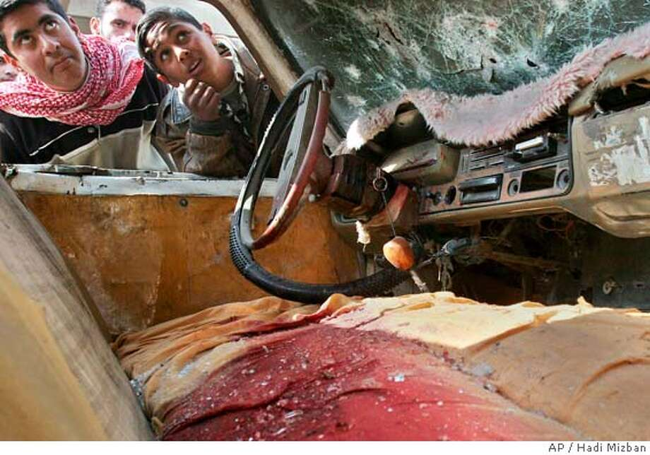 Two children peer through the window to look at the blood-soaked front cabin of a car hit by the blast from a car bomb which exploded in front of a hospital in the mostly Shiite town of Musayyib, about 55 kilometers (35 miles) south of Baghdad Saturday, Feb. 12, 2005, killing 17 and wounding 21, police and hospital officials said. The attack came a day after 23 people were killed in two attacks aimed at the Shiite community. (AP Photo/Hadi Mizban) Photo: HADI MIZBAN