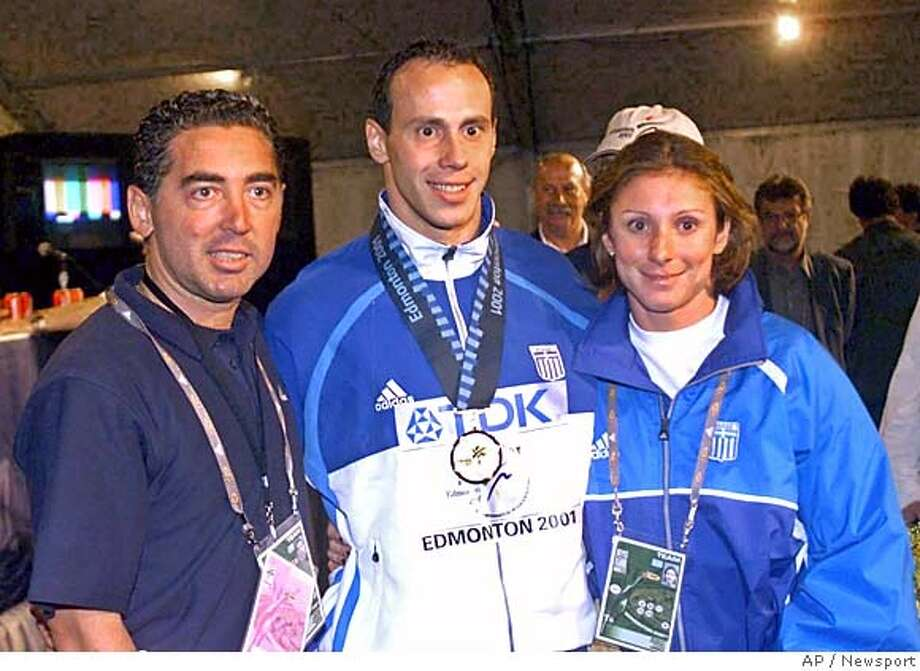 ** FILE ** This is an August 9, 2001 file photo of Greek athletes Kostas Kenteris, center, and Katerina Thanou, the 100-meter silver medalist in Sydney, right with their coach Christos Tsekos taken at the World Championships in Edmonton, Canada. Kenteris and Thanou have been pulled off the team for the Athens Games for missing drug tests, the Greek Olympic Committee said Saturday. (AP Photo/Newsport)