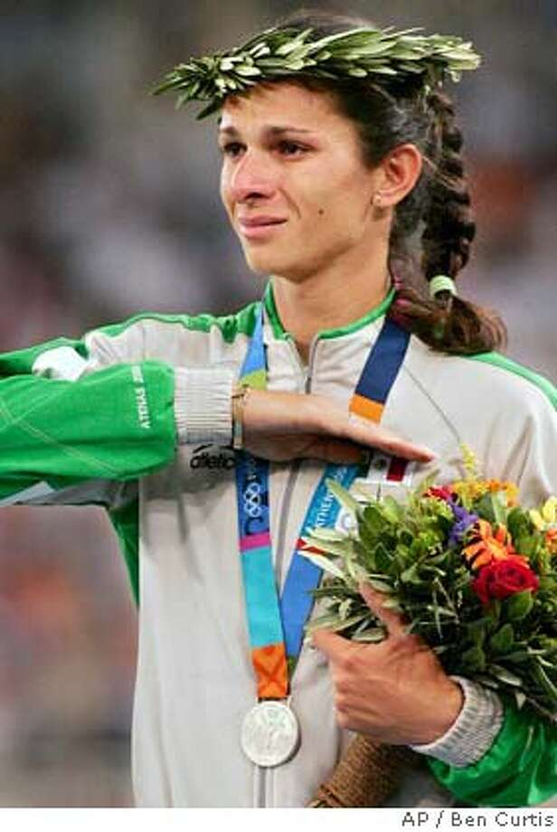 Silver medalist Ana Guevara, of Mexico, reacts on the medal stand after 400m at the 2004 Olympic Games Tuesday, Aug. 24, 2004 in Athens, Greece.(AP Photo/Ben Curtis) Photo: BEN CURTIS