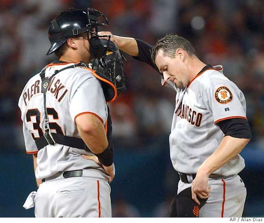 San Francisco Giants pitcher Wayne Franklin, right, wipes his forehead as he talks to catcher A.J. Pierzynski, left, after Florida Marlins' Mike Lowell hit a duble with the bases loaded in the first inning Tuesday, Aug. 24, 2004 in Miami. (AP Photo/Alan Diaz) Photo: ALAN DIAZ