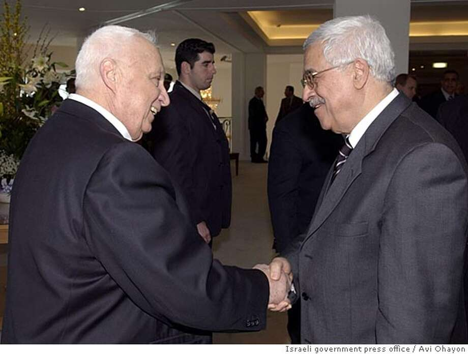 Israeli Prime Minister Ariel Sharon (L) shakes hands with Palestinian President Mahmoud Abbas during their meeting at Sharm el-Sheikh, February 8, 2005. Israeli and Palestinian leaders are expected to announce a ceasefire at a summit on Tuesday that could end over four years of bloodshed in which more than 4,000 people have died. (ISRAEL OUT) REUTERS/Avi Ohayon/ Israeli government press office 20050208 Photo: HO