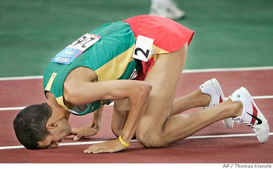 Hicham El Guerrouj, of Morocco, drops to his knees and touches his face to the track after he wins the 1500m at the 2004 Olympic Games Tuesday, Aug. 24, 2004 in Athens, Greece. (AP Photo/Thomas Kienzle) Ran on: 08-25-2004  After his tight win in the 1,500, Hicham El Guerrouj kisses the track before finding his baby daughter in the stands and kissing her too. Ran on: 08-25-2004  After his tight win in the 1,500, Hicham El Guerrouj kisses the track before finding his baby daughter in the stands and kissing her too. Photo: THOMAS KIENZLE
