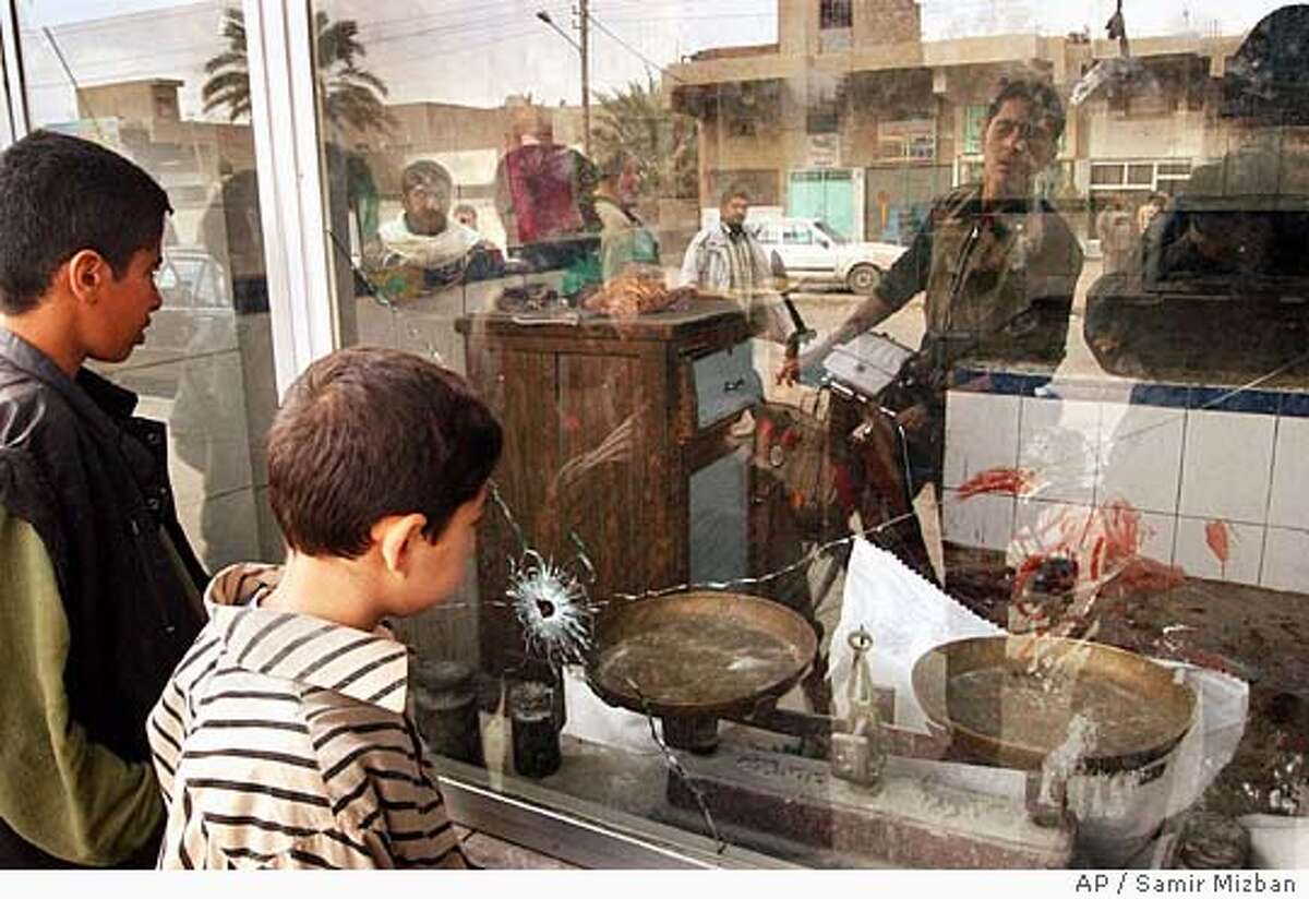 Two boys look at the scene of a shooting in a bakery in the New Baghdad area of Baghdad, Friday, Feb. 11, 2005. Masked gunmen opened fire on a crowd at a Baghdad bakery Friday, killing 11 people, police and witnesses said. (AP Photo/Samir Mizban)