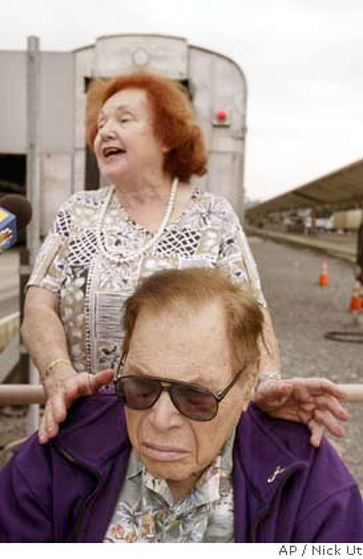 """Carl Barstow and his wife, Stephanie, wait to board a train at Union station in Los Angeles, Monday, Aug. 23, 2004, en route to Canada protesting against high U.S. drug prices. The """"Rx Express"""" was arranged by a taxpayers' group to take 25 senior citizens, small business owners and others on a trip to dramatize the group's call for the government to negotiate a national bulk-purchasing program for pharmaceuticals to reduce their cost to Medicare patients and others. (AP Photo/Nick Ut)"""