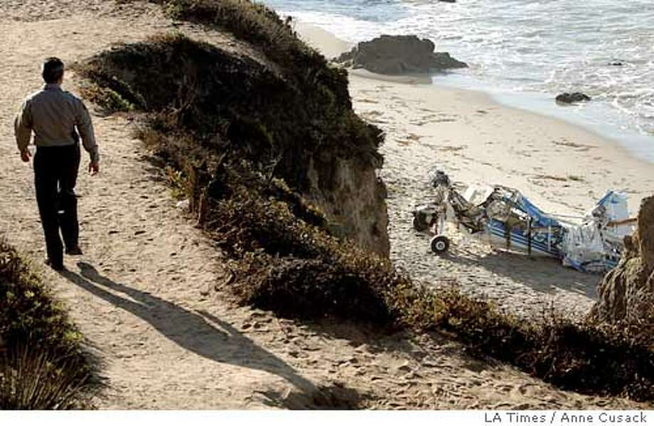 An unidentified official walks along a bluff Monday, Aug. 23, 2004, above the remains of a light plane, right, which washed ashore, after it collided with another plane Sunday, on El Matador State Beach near Malibu, Calif. Three people were killed in the accident. (AP Photo/Los Angeles Times, Anne Cusack) ** MANDATORY CREDIT ** Ran on: 08-24-2004  Photo caption Photo: ANNE CUSACK