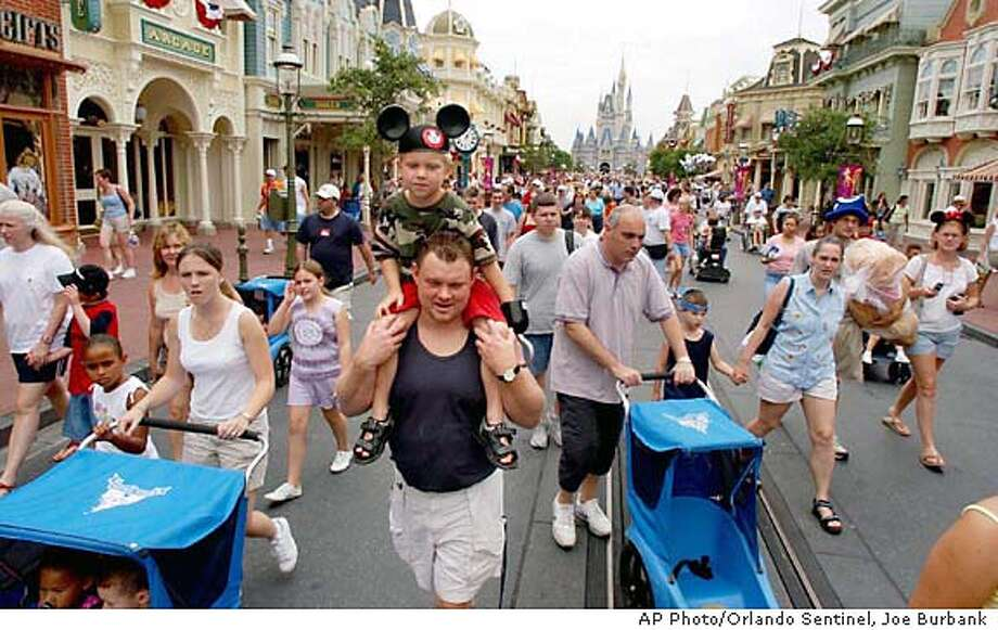 "Bill Heller, center, of Rockford, Ill., carries his son, Alex, 6, as thousands of guests at the Magic Kingdom at Walt Disney World near Orlando, Fla., exit the park on Main Street USA after an announcement was made that the park was closing at 1pm due to ""inclement weather,"" Friday, Aug. 13, 2004. Hurricane Charley was forecast to hit Central Florida later in the day. (AP Photo/Orlando Sentinel, Joe Burbank) Photo: JOE BURBANK"