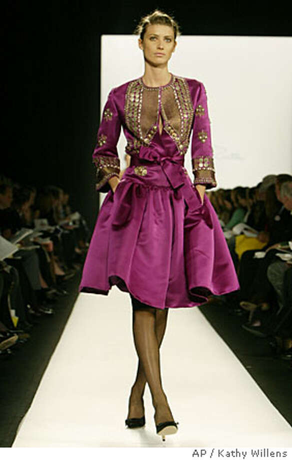 A model wears a fuchsia embroidered satin coat with black satin pumps, Monday, Feb. 7, 2005, during the presentation of the Oscar de la Renta Fall 2005 collection in New York. (AP Photo/Kathy Willens) Photo: KATHY WILLENS