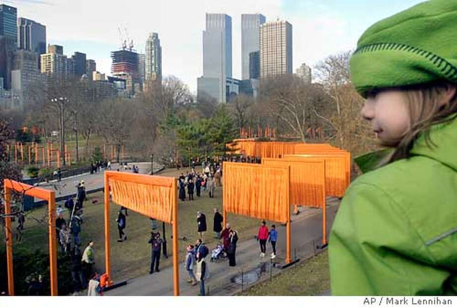 "Grace Kyrk, 7, of Cambridge, Mass., watches as workers unfurl "" "" project in New York's Central Park, Saturday Feb. 12, 2005. With flowing fabric the color of a sunrise, "" ,"" a massive public art installation in Central Park, was unfurled Saturday for the start of a 16-day stay transforming miles of footpaths in Central Park. (AP Photo/Mark Lennihan) Photo: MARK LENNIHAN"