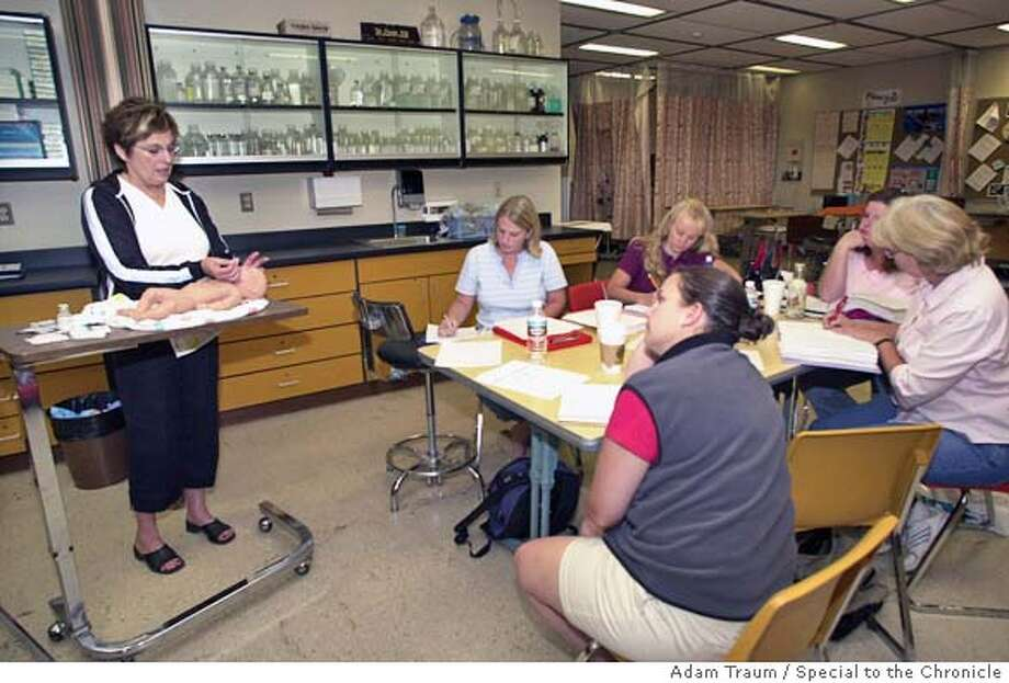 Maggie Siefert, left, demonstrates a procedure on a teaching doll to a nursing class at Napa Valley College 8/17/04. With heavy demand for health sciences campuses are getting overcrowded. .  Napa on 8/17/04 by Adam Traum Photo: Adam Traum