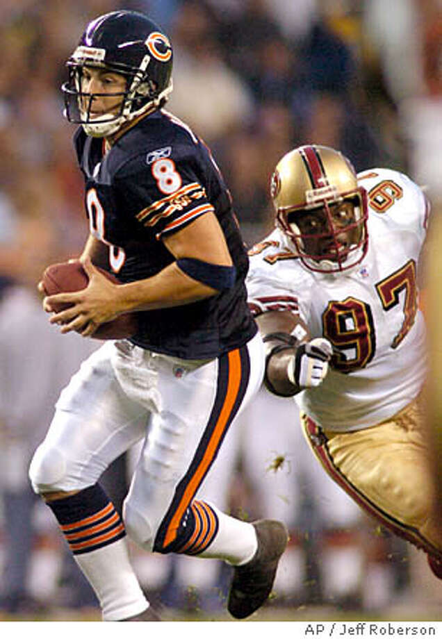 Chicago Bears quarterback Rex Grossman (8) scrambles past San Francisco 49ers' Bryant Young (97) during the first quarter of a preseason game Saturday, Aug. 21, 2004 in Chicago. (AP Photo/Jeff Roberson) Photo: JEFF ROBERSON