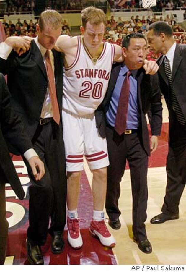Stanford guard Dan Grunfeld is helped off the floor by trainers Tomoo Yamada, right, and Jon Surface, left, as coach Trent Johnson, far right, looks on after Grunfeld injured his right knee during the second half against California, Saturday, Feb. 12, 2005, in Stanford, Calif. Stanford beat Cal 71-56. (AP Photo/Paul Sakuma) Photo: PAUL SAKUMA