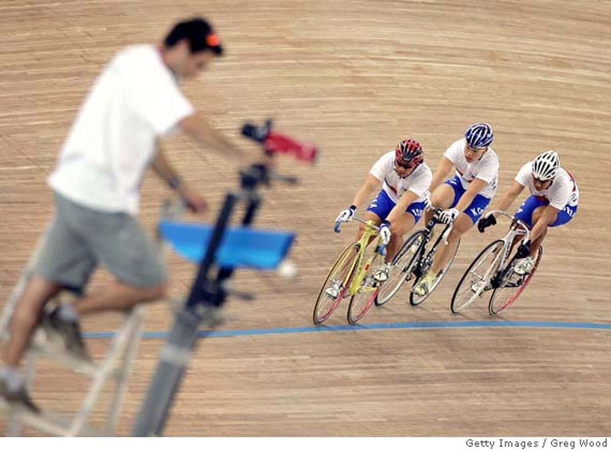 A worker aligns the photo finish camera as Korean riders practice during a training session at the Velodrome in Athens, 19 August 2004, on the eve of the start of the cycling track competition at the 2004 Olympic Games. AFP PHOTO GREG WOOD (Photo credit should read GREG WOOD/AFP/Getty Images) DV