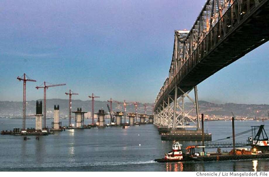 bridge040_lm  Event on 11/22/04 in Yerba Buena island.  The eastern span of the Bay Bridge, with the cranes where the new span is being constructed. A tug pushes a boat under the span at bottom right. This photo is from Yerba Buena Island.  Liz Mangelsdorf / The Chronicle MANDATORY CREDIT FOR PHOTOG AND SF CHRONICLE/ -MAGS OUT Photo: Liz Mangelsdorf