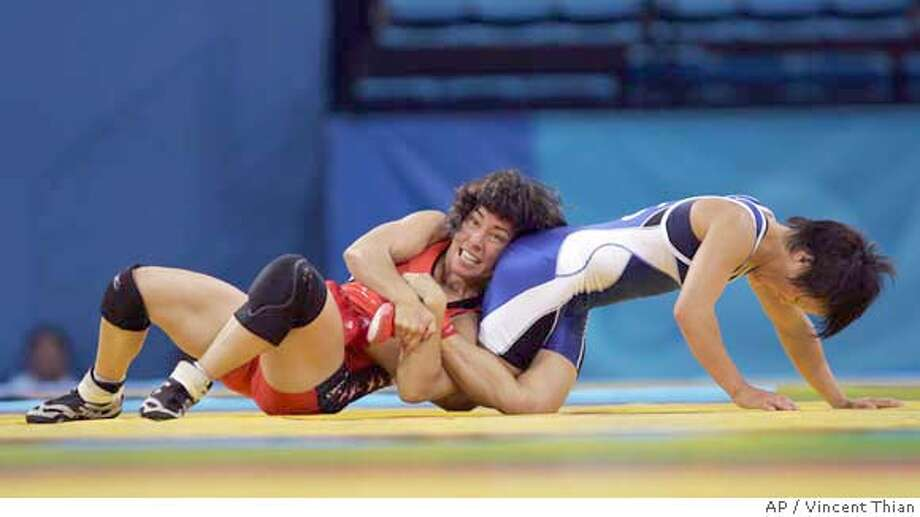 Patricia Miranda, left, from USA, and Li Hiu from China's wrestle during the women's pool elimination freestyle 48kg wrestling event at the 2004 Olympic Games in Athens, Sunday, Aug. 22, 2004. Miranda won. (AP Photo/Vincent Thian) Photo: VINCENT THIAN