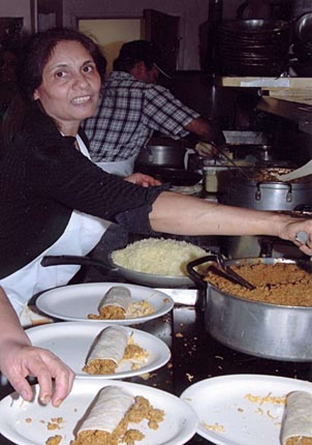 Kala Ubhi of Avatar�s Punjabi Burritos in Mill Valley dishes out turkey enchiladas for the restaurant's annual Thanksgiving giveaway.