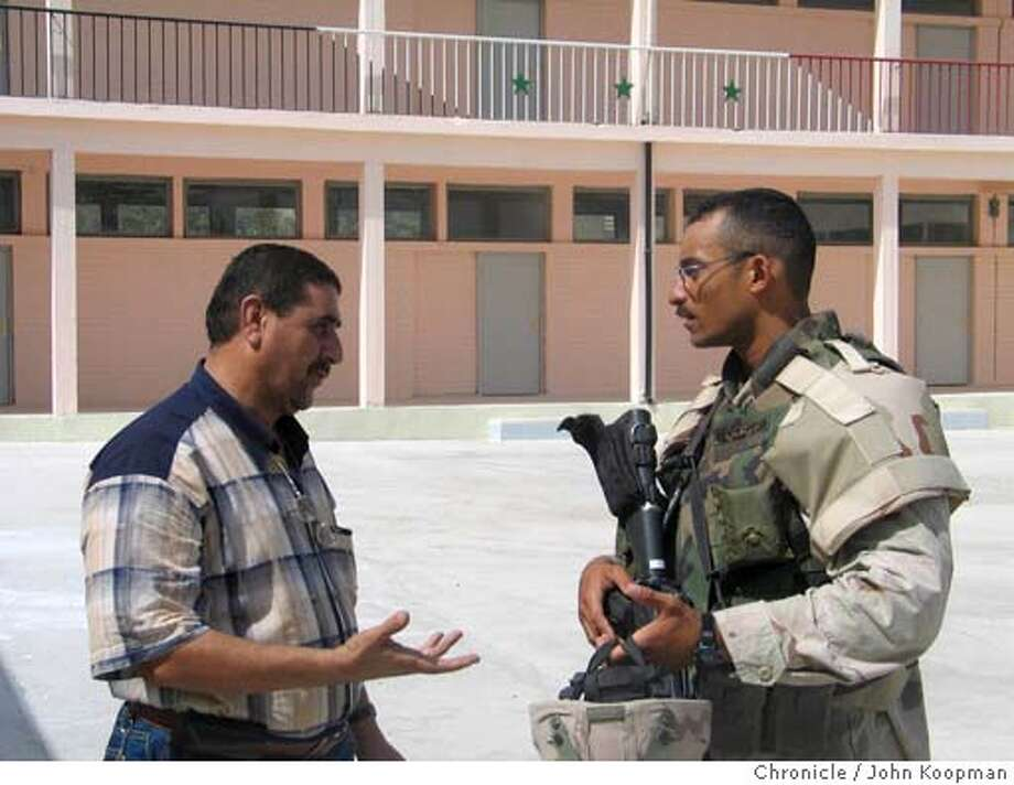 Sgt. Abu-Baker Senge, right, discusses a school renovation with Iraqi contractor Hazem Habib. Chronicle photo by John Koopman