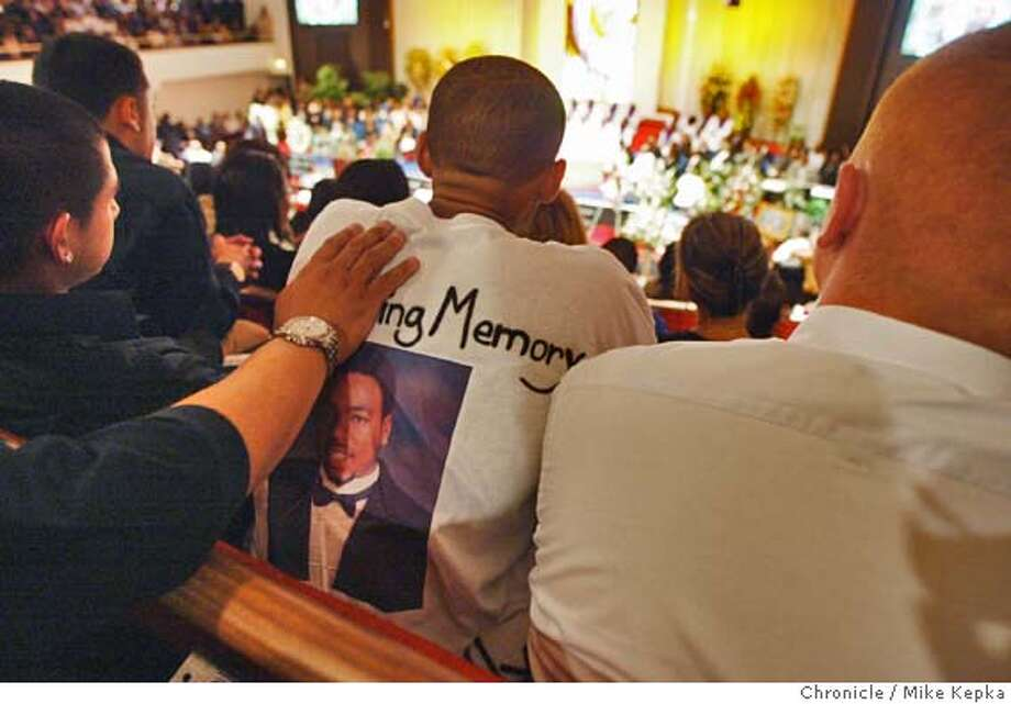 De La Salle graduating classmate,Kye Dohrmann, 17, recieves a warm hand from his father Danny Dohrmann during the funeral service for Terrecne Kelly.  Friends family and community members gather at the Hilltop community Church Wednesday for the funeral of Terrance Kelly, a promising local football player, who was shot and killed last week in Richmond.  MIKE KEPKA/The Chronicle Photo: MIKE KEPKA