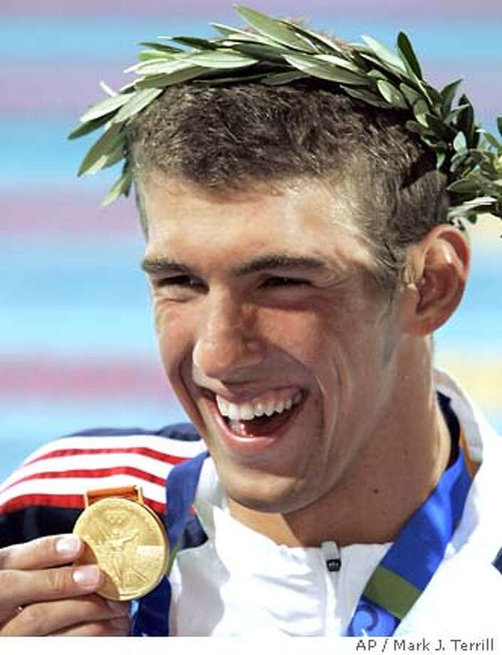 Michael Phelps, of the United States, smiles with his gold medal after winning the 100-meter butterfly at the Olympic Aquatic Centre during the 2004 Olympic Games in Athens, Friday, Aug. 20, 2004. (AP Photo/Mark J. Terrill) Photo: MARK J. TERRILL