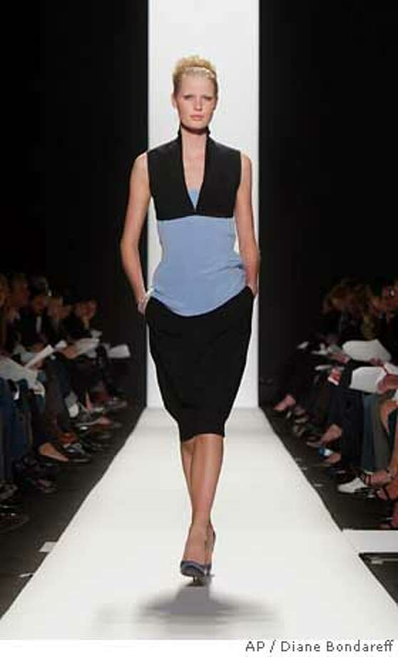 A black double constructed wool suit and a sky blue silk tank is modeled during the Narciso Rodriguez Fall Winter 2005 fashion show, Tuesday, Feb. 8, 2005, in New York. (AP Photo/Diane Bondareff) Ran on: 02-10-2005  Narciso Rodriguez's collection includes a black wool suit paired with a silk tank top. Photo: DIANE BONDAREFF