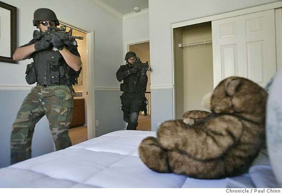 A teddy bear watches the activity as SWAT officers do a room-by-room search through a model home during an exercise. The Tracy police dept. SWAT team will take over new home models at Hillstone at Lourence (cq) Ranch development for an all-day training session in Tracy on 8/20/04. PAUL CHINN/The Chronicle Photo: PAUL CHINN