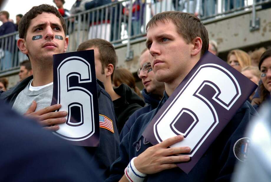 "UConn seniors Craig Woodhouse, left, and Brian Keenan hold ""6"" signs in honor of Jasper Howard's jersey number before the start of Saturday's contest against Rutgers. Photo: Autumn Driscoll / Connecticut Post"